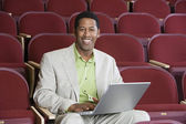 Happy Businessman Using Laptop In Auditorium — Stock Photo