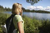 Femme avec des jumelles au lac — Photo