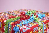 подарок завернутый с красочной бумаги и фигурные лентой — Стоковое фото