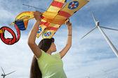 Chica sosteniendo avión cometa en el parque eólico — Foto de Stock