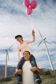 Girl Sitting On Father's Shoulders At Wind Farm — Stock Photo