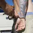 Stock Photo: Officer Handcuffing Tattooed Young Man