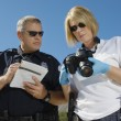 Stock Photo: Police Officer And Investigator With Camera