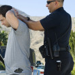 Police Officer Arresting Young Man — Stock Photo #21800495