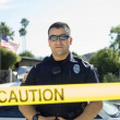 Police Officer Standing Behind Caution Tape — Stock Photo #21800521
