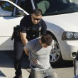 Police Officer Arresting Young Man — Stock Photo #21800751