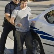 Police Officer Arresting Young Man — Stock Photo #21800769