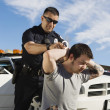 Stock Photo: Police Officer Arresting Young Man