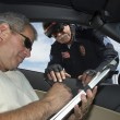 Police officer watching driver sign papers - Stock Photo