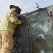 Stock Photo: Firefighter Inspecting Crashed Car