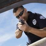 Police Officer Aiming Gun Through Car Window — Stock Photo