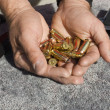 Man's hands holding bullets by guns — Stock Photo