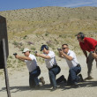 Stock Photo: Four Firing Guns At Shooting Range