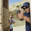 Two Men Aiming Hand Guns At Firing Range - Stok fotoraf