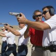 Instructor Assisting Officers With Hand Guns At Firing Range — Stockfoto