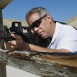Man Aiming Machine Gun At Firing Range - Lizenzfreies Foto