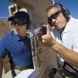 Stock Photo: Instructor Assisting MWith Hand Gun