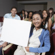 Teacher Holding Billboard With Students In The Background - Stock Photo