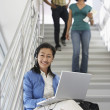 Professor Using Laptop While Students Walking Down Staircase — Stock Photo