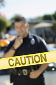 Police Officer Standing Behind Caution Tape — Stock Photo