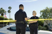 Police Officers Separated By Caution Tape — Stock Photo