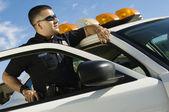 Oficial de policía apoyándose en patrulla — Foto de Stock