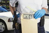 Police Officer Putting Money in Evidence Envelope — Stock Photo