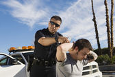 Police Officer Arresting Young Man — Stock Photo