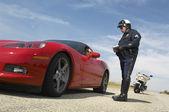 Policía de tránsito hablando con el conductor del coche de los deportes — Foto de Stock