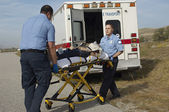 Paramedics Transporting Victim On Stretcher — Stock Photo