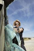 Female Police Officer Aiming Gun Through Broken Windshield — Stock Photo