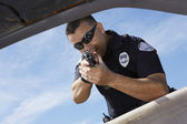 Police Officer Aiming Gun Through Car Window — Stock Photo