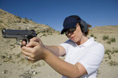 Woman Aiming Hand Gun At Firing Range In Desert — Stock Photo