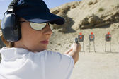 Woman Aiming Hand Gun At Firing Range — Stock Photo
