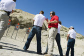Instructor Assisting Aiming Guns At Firing Range — Stock Photo
