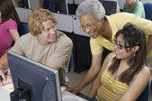 Happy Senior Teacher Assisting Students — Stock Photo