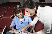 Teacher Assisting Male Student In Classroom — Stock Photo