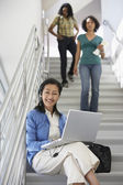 Profesor usando laptop mientras los estudiantes caminando por escalera — Foto de Stock