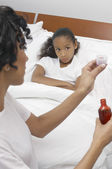 Woman Giving Cough Syrup To Daughter In Bed — Stockfoto