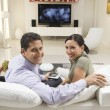 Couple With Remote Control Sitting On Sofa — Stock Photo