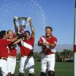 Polo team celebrating with trophy on field — Stock Photo