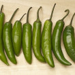 Green Chili Peppers In Row - Stock Photo