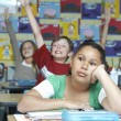 Bored Girl With Classmates Raising Hands In Background — Stockfoto