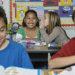 Schoolgirls chatting in classroom — Stock Photo