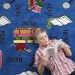 Boy Reading Book On Floor — Stock Photo
