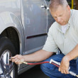 Mechanic Inflating RVs Tire - Stock Photo
