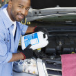 Stock Photo: Auto Mechanic Adding Fluids To Minivan