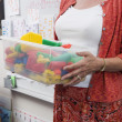 Teacher Holding A Box Full of Plastic Puzzle Pieces — Stock Photo