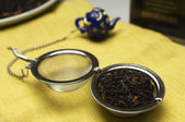Dry Tea Leaves In Strainer On Table Napkin — Stock Photo