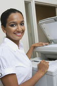 Businesswoman Using Fax Machine In Office — Stock Photo